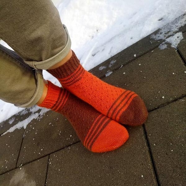 dwukolorowe pomaranczowo brazowe skarpetki robione na drutach model krufka socks na tle sniegu
