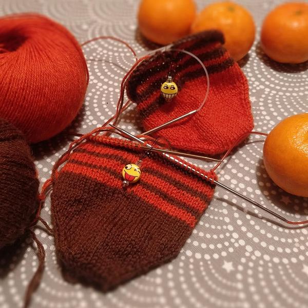 skarpetki na drutach w trakcie dziergania na drutach z zylka Perfrormance Cool Wool terakota i braz oraz znaczniki dziewiarskie w ksztalcie emotek